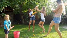 愉快的快乐的家庭慢动作英尺长度获得乐趣在有水枪和水管的庭院 飞溅水  股票视频