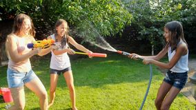 愉快的快乐的家庭慢动作英尺长度获得乐趣在有水枪和水管的庭院 飞溅水  股票录像
