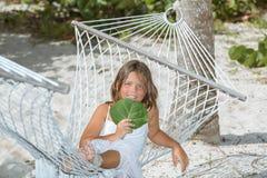 愉快的快乐的小女孩坐吊床在热带庭院里 免版税库存照片