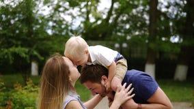 愉快的快乐的年轻家庭父亲、母亲和小儿子获得乐趣户外,一起使用在夏天公园