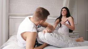 愉快的快乐的爱恋的夫妇有枕头战在坐在睡衣的床、人和女孩 影视素材