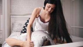 愉快的快乐的爱恋的夫妇有枕头战在床、年轻可爱的坐在睡衣的人和女孩,慢动作 股票录像
