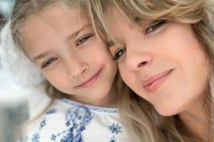愉快的快乐的美丽的年轻母亲特写镜头画象有她的小微笑的女儿的 库存照片