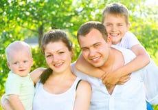 愉快的快乐的年轻家庭在夏天公园 免版税库存照片