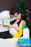 愉快的怀孕的夫妇临近圣诞树 免版税库存照片