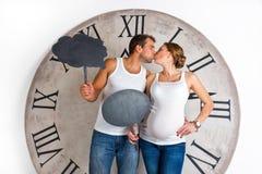 愉快的怀孕的夫妇在亲吻和显示标志讲话泡影的白色穿戴了 免版税库存照片