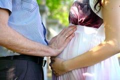 愉快的怀孕的夫妇在夏天公园 免版税库存照片