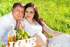 年轻愉快的怀孕的夫妇在开花的春天停放 免版税库存照片