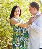 年轻愉快的怀孕的夫妇在开花的春天停放 免版税库存图片