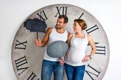 愉快的怀孕的夫妇在白色显示的标志讲话泡影穿戴了 库存图片