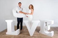 愉快的怀孕的夫妇在白色的白色穿戴了 库存照片
