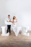 愉快的怀孕的夫妇在白色背景的白色穿戴了 免版税库存照片