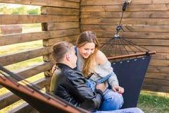 愉快的怀孕的夫妇坐在吊床的-家庭、父母身分和幸福概念 库存图片