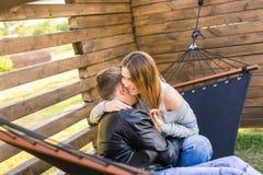 愉快的怀孕的夫妇坐在吊床的-家庭、父母身分和幸福概念 库存照片