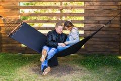 愉快的怀孕的夫妇坐在吊床的-家庭、父母身分和幸福概念 免版税库存图片
