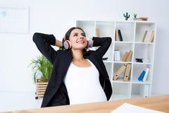 愉快的怀孕的女实业家放松的和听的音乐在办公室用手 免版税库存图片