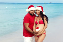 愉快的怀孕,怀孕的家庭 圣诞节服装和圣诞老人帽子的预期父母在海 免版税图库摄影