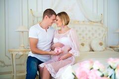 愉快的怀孕:举行婴孩赃物的丈夫在腹部附近他怀孕的妻子 库存图片