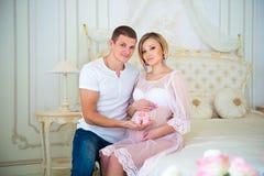 愉快的怀孕:举行婴孩赃物的丈夫在腹部附近他怀孕的妻子 免版税图库摄影