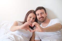 愉快的恋人结合感觉的舒适在床上 库存图片