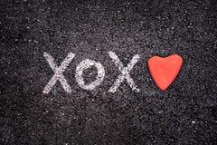 愉快的情人节卡片、xoxo在地面上和心脏石头 免版税库存图片