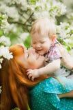 愉快的愉快的母亲画象和儿子在春天从事园艺 免版税库存照片
