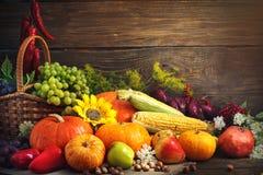愉快的感恩天背景、木桌装饰用南瓜,玉米、果子和秋叶 免版税库存照片