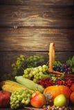 愉快的感恩天背景,木桌,装饰用蔬菜、水果和秋叶 秋天背景特写镜头上色常春藤叶子橙红 免版税库存图片