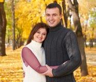 愉快的成人夫妇容忍在秋天城市公园、树与黄色叶子,明亮的太阳和愉快的情感、柔软和感觉 图库摄影