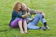 愉快的成人男人和妇女坐与电话的草 免版税库存照片