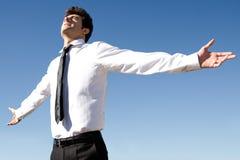 愉快的成功的商人举有天空的胳膊在backgr 库存照片