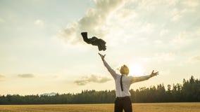 愉快的成功的商人在天空中的投掷他的外套 库存图片