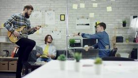 愉快的成功的商人在有的办公室乐趣投掷的文件 一个人播放guiter 他们是非常 股票视频