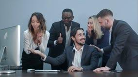 愉快的成功的多种族企业笑和欢呼他们的成功 免版税库存图片