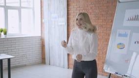 愉快的成功的妇女在她的办公室高兴在whiteboard附近 项目4K的成功的完成 股票录像