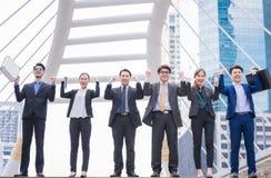 愉快的成功的集团人民递被上升的成功与与胳膊的城市背景成功的集团 免版税库存照片