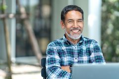 愉快的成熟人画象有看照相机的白色,灰色时髦的短的胡子的室外 退休的拉美裔偶然生活方式  免版税库存照片