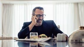 愉快的成熟商人谈话在手机,当坐dinning的桌在酒店房间时 吃的商人午餐和 库存图片