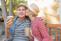 愉快的成熟在一条长凳的夫妇饮用的咖啡在城市 免版税库存照片