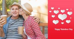 愉快的成熟在一条长凳的夫妇饮用的咖啡的综合图象在城市 免版税库存图片
