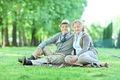 愉快的成熟夫妇坐一条毯子在公园 免版税库存图片