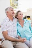 愉快的成熟夫妇坐长凳在城市 库存图片