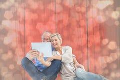 愉快的成熟夫妇的综合图象使用片剂个人计算机的 图库摄影