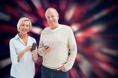 愉快的成熟夫妇的综合图象使用他们的智能手机的 免版税图库摄影