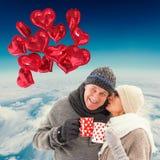 愉快的成熟夫妇的综合图象在冬天给拿着杯子穿衣 库存图片