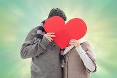 愉快的成熟夫妇的综合图象在冬天给拿着红色心脏穿衣 免版税库存照片