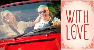愉快的成熟夫妇的综合图象在红色敞蓬车的 库存图片