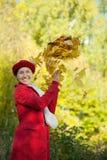 愉快的成熟妇女投掷的槭树叶子 库存图片