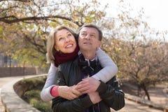 愉快的成熟家庭夫妇拥抱的燕麦公园 库存图片