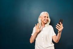 愉快的成熟老妇人谈话与朋友通过手机挥动 库存图片
